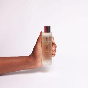 Malée Natural Science Verdure Moisturising Oil hand holding bottle upright on grey background