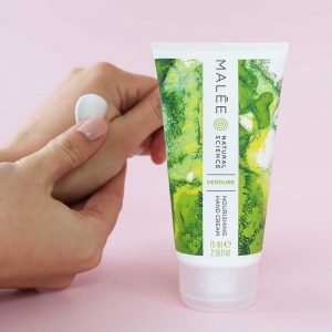 Malée Natural Science Verdure Nourishing Hand Cream applied on to hands with nude nail polish on pink background
